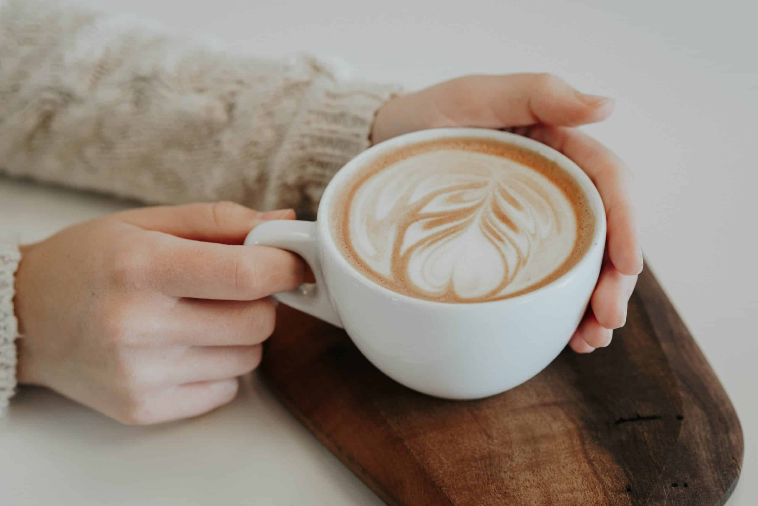 A person holding a cup of coffee with both hands.